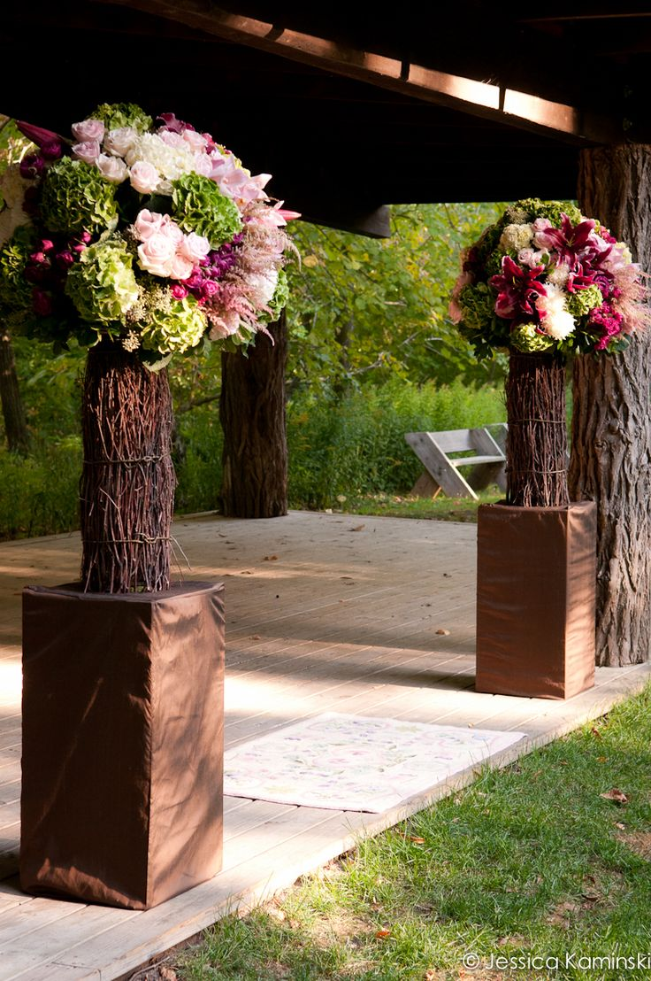 Outdoor ceremony designs with branch embellished vases and over-sized floral designs to anchor the ceremony space at Milwaukee's own Schlitz Audubon Nature Center. Flowers include hydrangea, roses, orchids, astilbe, and greenery for texture. Wedding Floral by freshdesign. Photography - Jessica Kaminski Photographer.