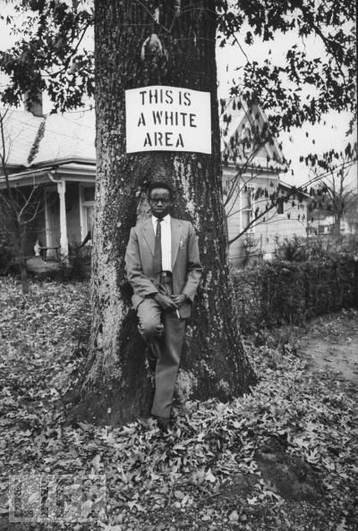 Georgia 1963: A Kenyan student from Morehouse College stands underneath a racist sign pinned to a tree. LIFE Magazine