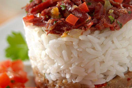 Receita de arroz arrumadinho feito de uma maneira diferente, com a base de tutu de feijão e coberto por um refogado de carne-seca. Experimente!