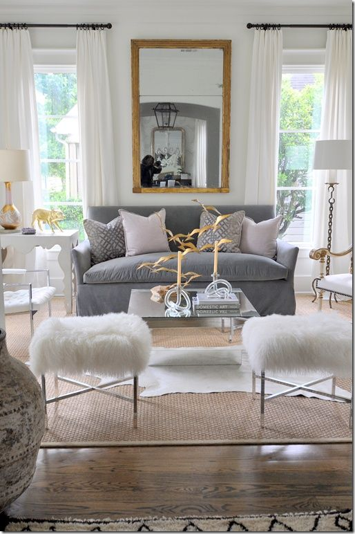 I love the silvers whites and greys. But the gold mirror frame is genius in this cool toned setting. silver would have disappeared. The gold is picked up subtly here and there in interesting accents. I think I would choose a different seat upholstery for the stools - not a big fake fur fan.