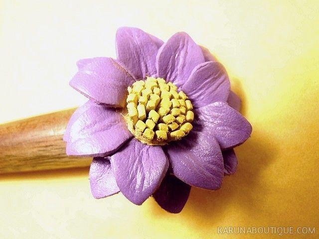 Détail d'un pic à cheveux fleur en bois et cuir violet - Artisanat équitable.