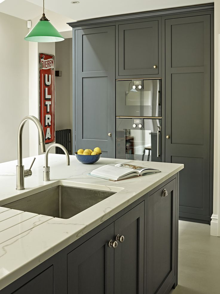 Dark Grey Black Shaker Kitchen Cabinets and Island with Grey-White Marble Effect Countertops and modern integrated sink with Quooker tap. Sleek wall-mounted anthracite Gaggenau oven and green pendant island lighting.