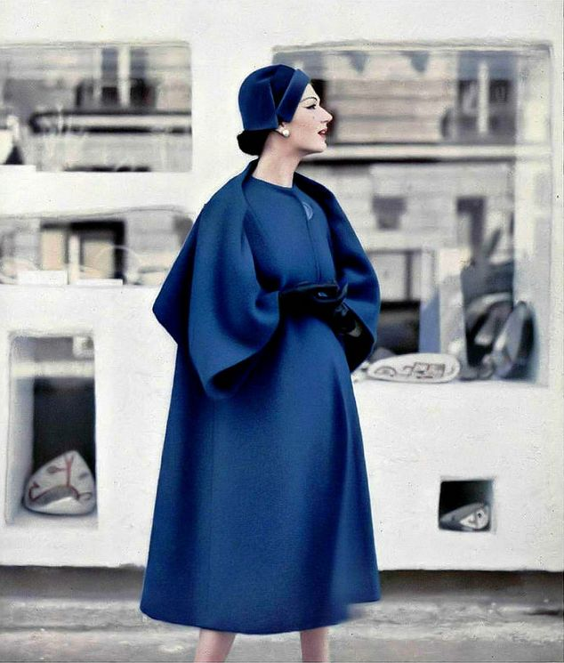 1957 Simone in roomy blue coat whose effect of short cape at the back is given by the cut and sleeve setting, collarless and one large button-closure, by Pierre Balmain, photo by Pottier