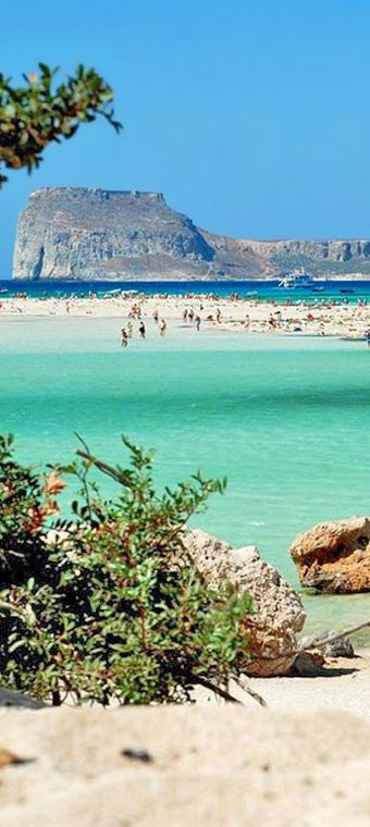 Hike down the rocky crags to the warm turquoise waters of Balos Beach. This white sand lagoon in Crete, Greece is a wonderful spot for swimming and sunbathing.