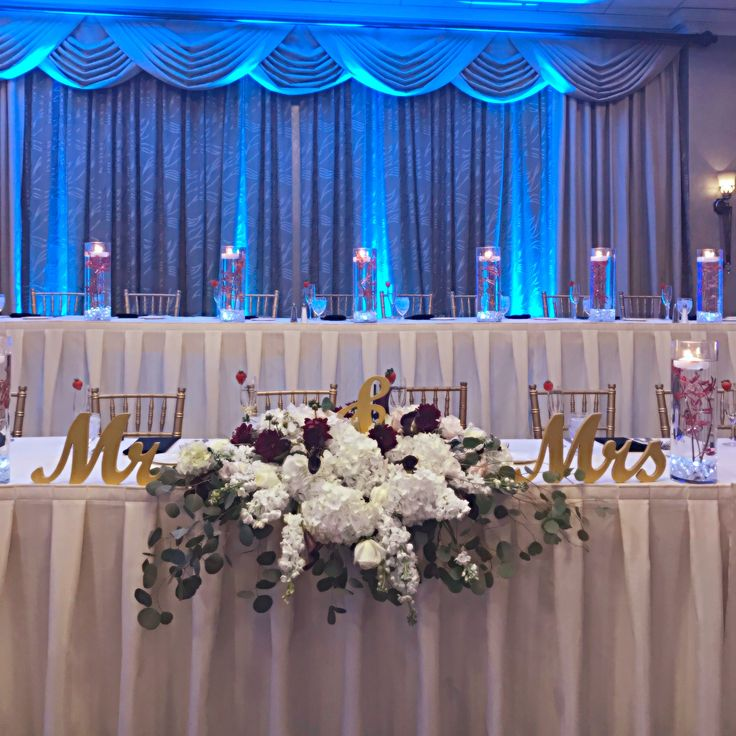 Glamorous Head Table and Gold Chiavari Chairs Decorated with Blue Uplighting , Mr & Mrs Sign , White and Red Floral Centerpiece in The Grand Ballroom at Valley Forge Casino Resort #Idovfcr