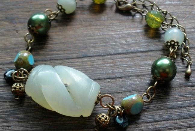 Náramok vo Vintage štýle. Hlavnú časť tvorí stredová mohutná vyrezávaná korálka zo zeleného avanturínu. Doplnená je zelenými perlami, brúsenými sklenenými ohňovkami, plôskovanými korálkami a diskami s travertínovým povrchom (imitácia kameniny), doplnené filigránovými guličkami a kaplíkami.