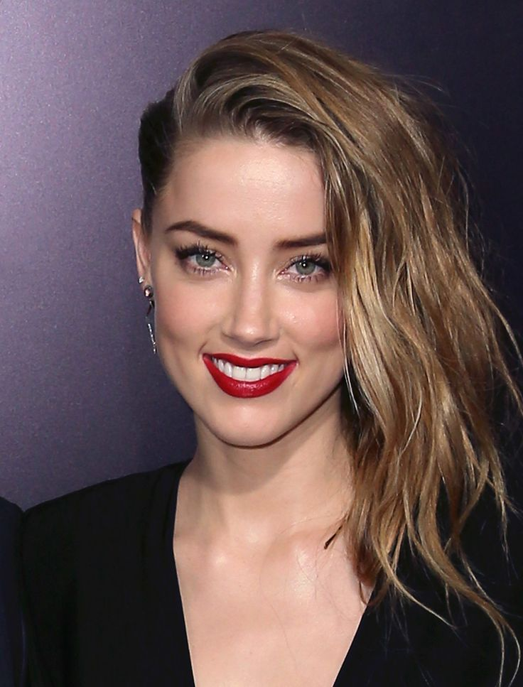 At the premiere of 3 Days to Kill, Amber Heard sizzled with filled-in brows and deep red lips.