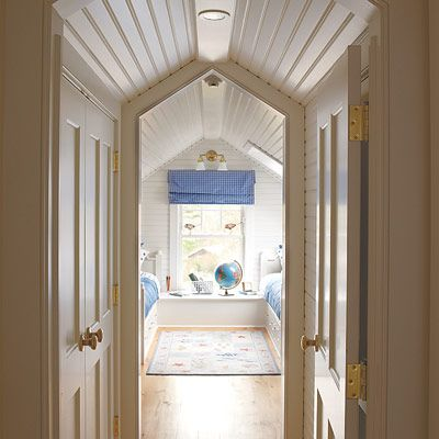 The hallway's vaulted ceiling extends to the door frames; when closed, the wall-height doors have triangles of space above them to channel air and light.