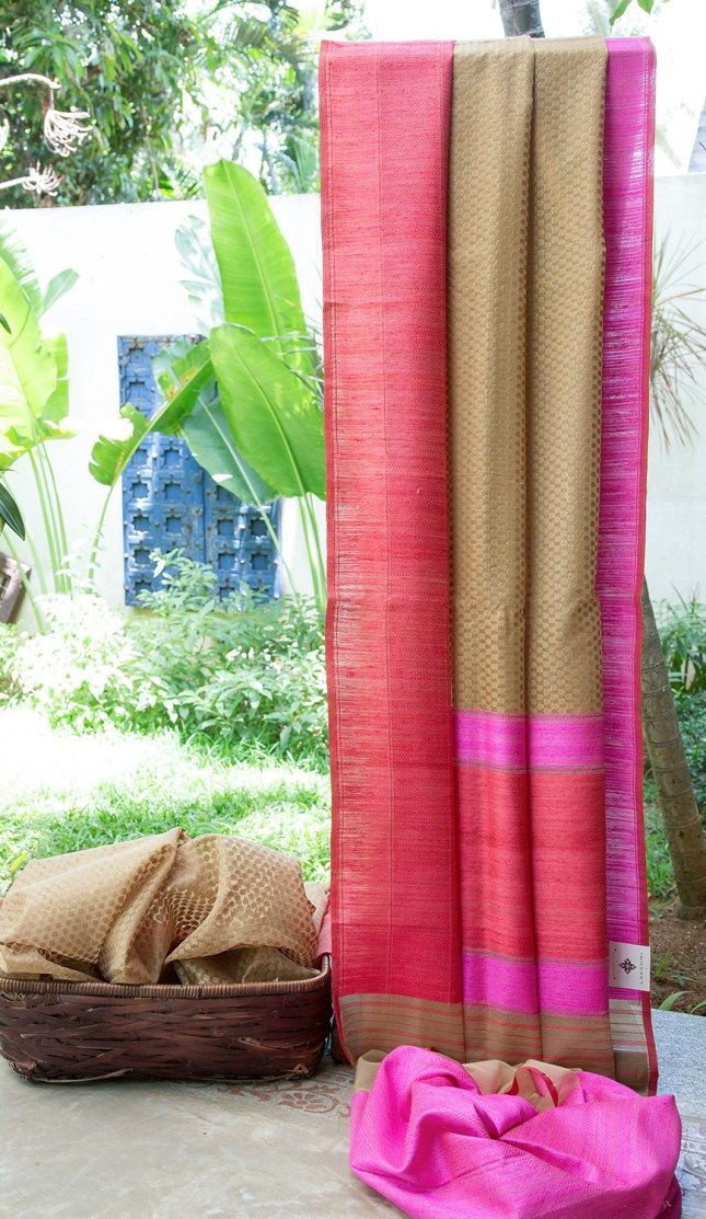 This fawn coloured Benares kora has a beautiful texture all along the sari. And complementing it are the border & pallu in Fuchsia pink and light crimson red giving it a very elegant finish.
