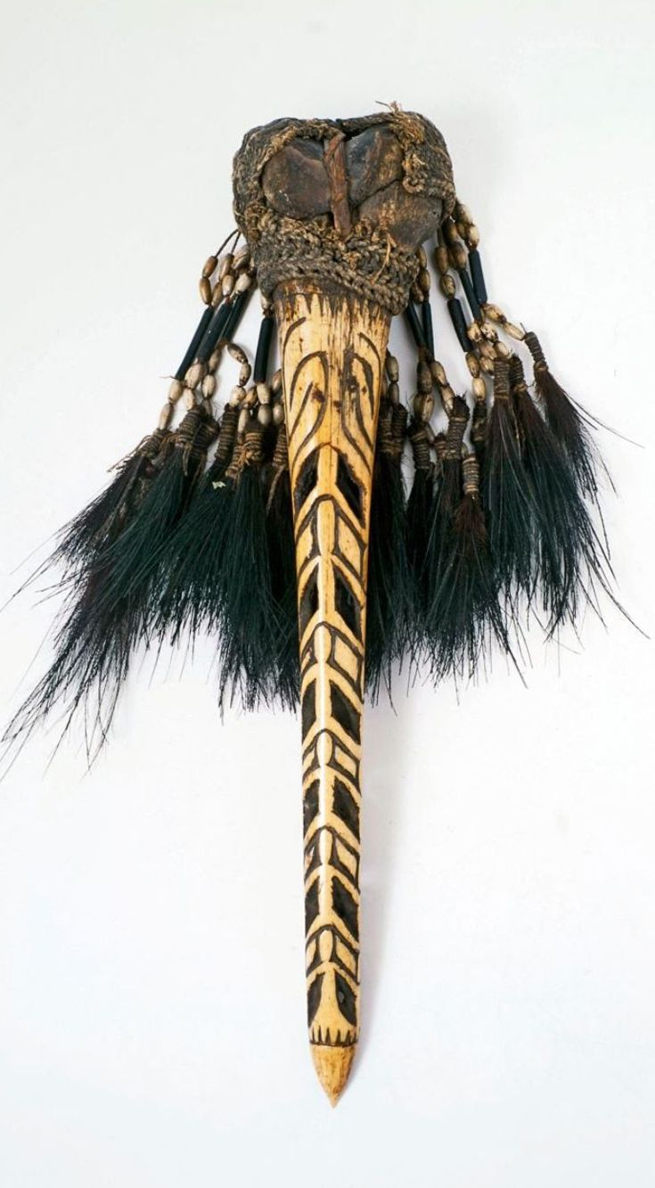 Papua (Indonesia) ~ Asmat, Atsy, Becembub | Dagger of carved from a human femur. Decorated with braids, white coix seeds and feathers of a cassowary. | Ornamental daggers such as these were worn on the upper arm of headhunters to project strength. | ca. 1957 or earlier