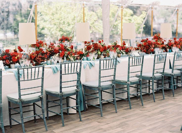 Long estate tables were dressed in lamplight and custom flaxen linen with verdigris velvet details and crimson centerpieces. photo: @tecpetaja | design: @calderclark | rentals: @snyderevents | flowers: @blossomsevents | #southernwedding #luxurywedding #plantationwedding