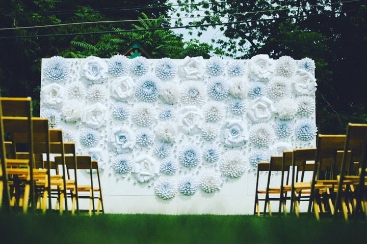 A stunning handmade flower wall featuring paper dahlias, roses and pompoms.