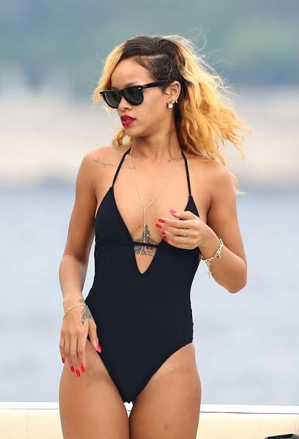 Rihanna Shows off pert derrière in a low-cut black swimsuit in Monaco