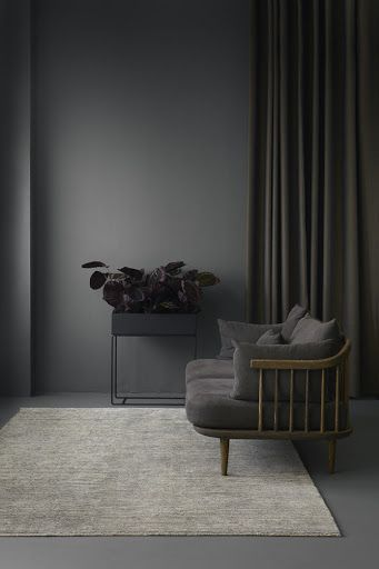 Beautiful grey monochrome room with a dark grey couch, a dark grey flower  pot, dark grey walls, a light grey rug and dark grey curtains.