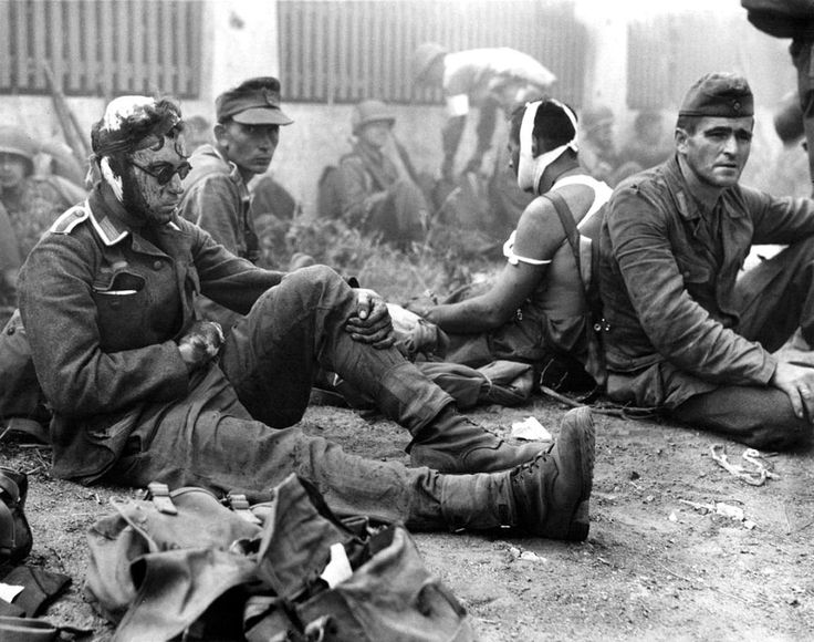 Wounded German soldiers taken as POWs by American troops during Operation Dragoon wait to be treated by medics at a collection point. Between Cavalaire-sur-Mer and Saint-Raphaël, Var, Provence-Alpes-Côte d'Azur, France. August 1944. By Henry L. Griffin.