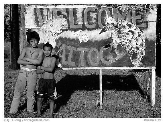 Children in front of a turtle a shark sign in Vaitogi. Tutuila, American Samoa