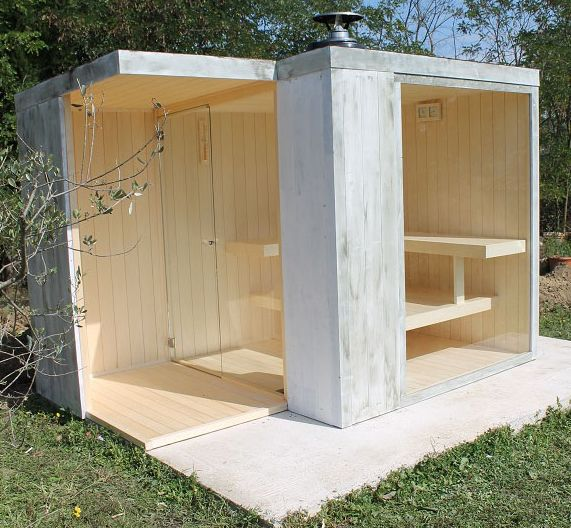 Casetta sauna con ampia vetrata e stufa a legna