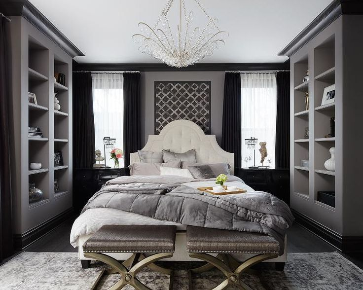 SuzAnn Kletzien - Chic bedroom features a white tufted bed dressed in gray shams and quilt flanked by glossy black nightstands adorned with gold knobs and Restoration Hardware 1920s Odeon Clear Glass Fringe Table Lamps placed under windows dressed in black curtains layered over white sheer drapery panels.