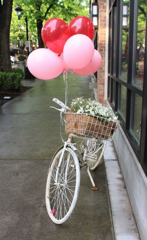 pink balloons tied to a white bike