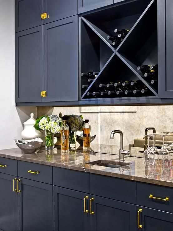 Glam wet bar boasts blue shaker cabinets adorned with brass pulls and knobs paired with brown marble countertops and an antiqued mirrored backsplash, A square wet bar sink and a satin nickel bar faucet stands under a navy blue crosscut wine rack.