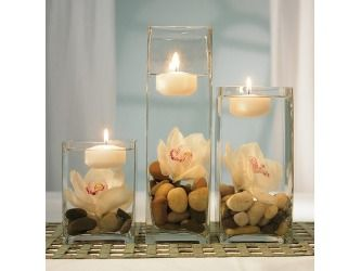 Rocks and flowers in vases with floating candles