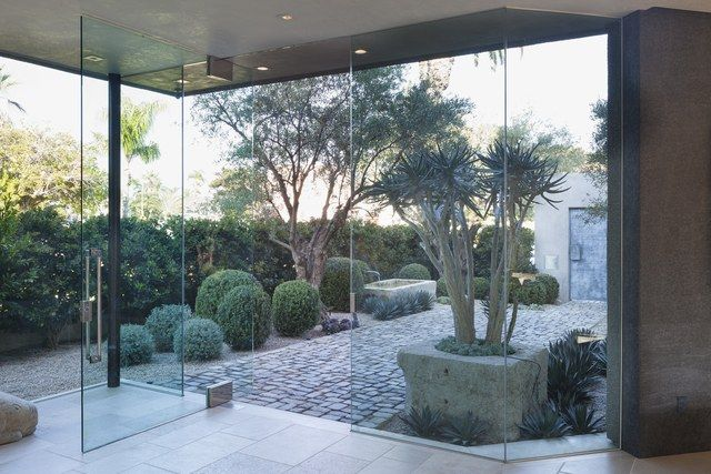 This glass-fronted home calls for an outdoor space that makes an impact indoors, too. Shrader achieved that by edging a cobblestone path with structural plantings, including agave and boxwood globes. Olive trees provide a bit of romance—and welcome shade.