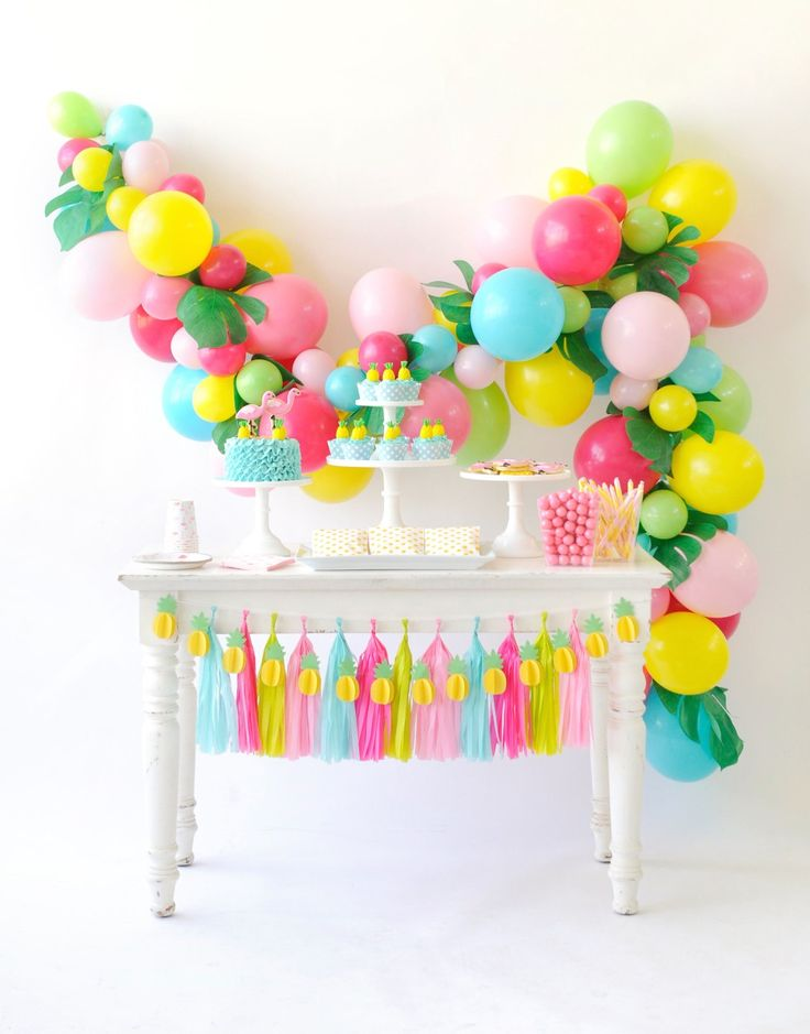 A colorful balloon and palm leaf wall garland, oh my! This backdrop is the perfect addition behind your flamingo birthday party dessert table. Decorate the table with pink, lime, and aqua paper tassels. Pineapple table garland. Flamingo Party styling by Happy Wish Company. Photography by Tammy Hughes Photography. Stationery by Minted artist, Laura Hankins.