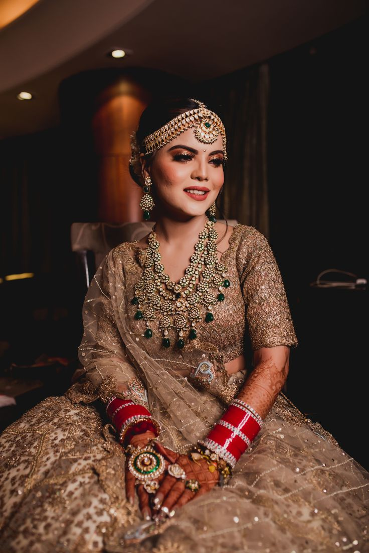 Bride In Gold Lehenga With Emerald Jewellery And Broad Matha Patti