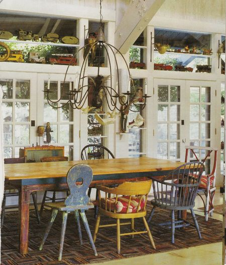 A Large Chandelier Hangs Over The Wooden Dining Table Which Is Surrounded  By An Assortment Of Rustic Dining Chairs