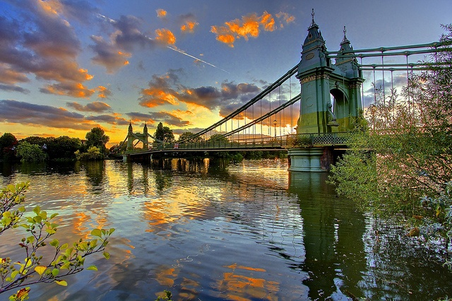 Hammersmith Bridge is a suspension bridge in west London. It allows road traffic and pedestrians to cross to Barnes, in the London Borough of Richmond upon Thames, on the south side of the river.   The construction of the actual bridge ended in 1887 and it is 210 m long and 13 m wide. This bridge is famous because it appeared in some scenes from the movie Sliding Doors filmed next to the bridge and in the Blue Anchor pub nearby.