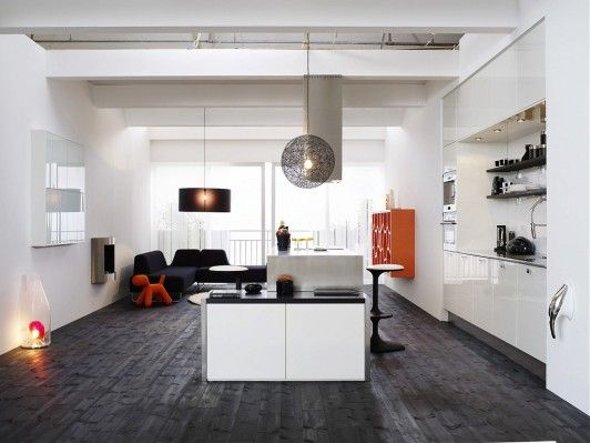 Interior Design Styles. Inspiring Scandinavian Home Interior Designs. Contemporary Scandinavian-Style Open-Plan Kitchen with Island Design Completed with Ceiling-Mounted Kitchen Chimney, Cool Black Bar Stools, Unique Black Hanging Pendant Lights, Glossy White and Orange Wall Storage Shelves, Cozy L-Shaped Dinner Space, and Amazing Dark Black Wooden Floor