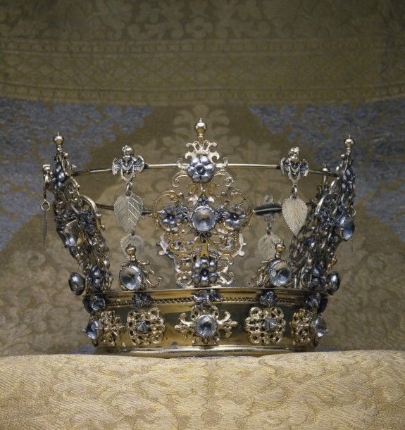 Wedding crowns in Scandinavia were worn by brides of all social strata. They were owned by the bride's parish and loaned for the occasaion. Wedding crowns were richly decorated with emblems of conjugal love: this example includes carnations, associated with enduring marriage because their fragrance outlasts their blossoms, dangling linden leaves, which represent fertility in Nordic literature, and angels, Christian figures that allude to the eternal and spiritual qualities of marriage.