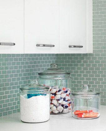 Oversized canisters and jars stylishly hold powder detergents, dryer sheets, clothespins, and more.