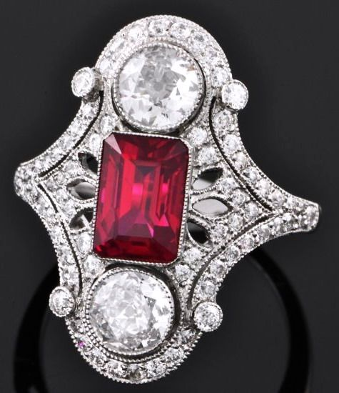 Art Deco Ruby and Diamond Dinner Ring.  Platinum ladies' dinner ring features one emerald-cut ruby, 2.32 carats, bezel-set at the center of a vintage-inspired pierced bar mounting. On the top and bottom of the ruby are two Old European-cut diamonds, also in bezel settings, and the three stones are accented by filigree and smaller round-cut diamonds.