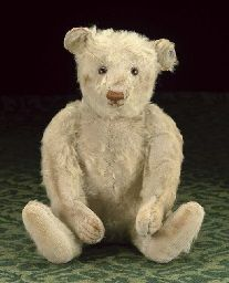 A Steiff teddy bear  with white mohair, brown and black glass eyes, pronounced muzzle, restitched light brown nose, mouth and claws, swivel head, jointed limbs, hump and FF button in ear, 1920s --16½in. (42cm.) high (bald patches, general thinning and wear, some staining to right arm, cheeks and nose, pads recovered) Price Realized   $959 Estimate $533 - $888