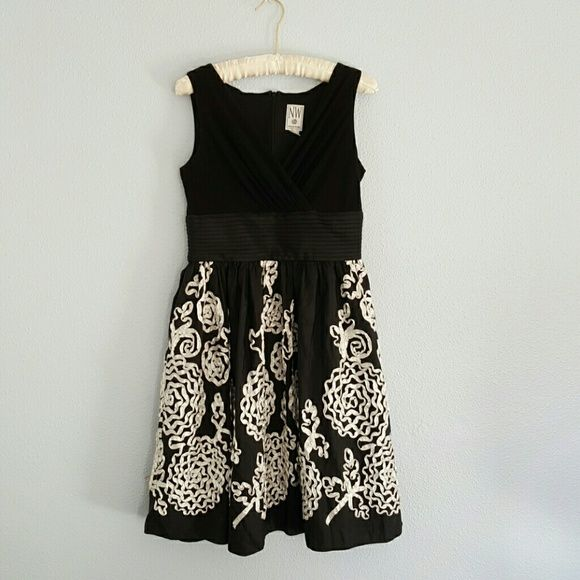 Knee length black dress with white floral Beautiful white ribbon floral design on the bottom half of a formal black dress. Great condition, I have only worn it twice. So cute with a slight body to the skirt. Night Way Collections (NW) Dresses Midi