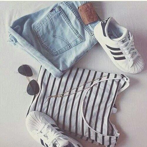 Maglia a righe bianca e nera. Scarpe da ginnastica bianche e nere. Pantaloncini di jeans. Occhiali da sole.