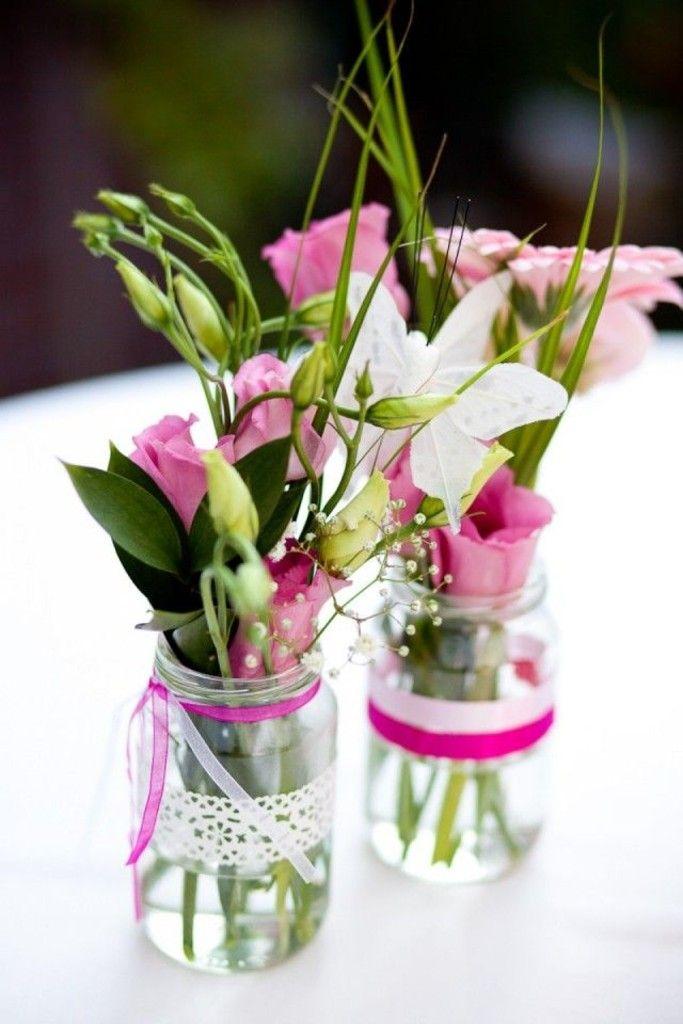 Bloemenvaasjes. Elke statafel: een potje bloemen en potje theelichtje op een boomschors met een hartje.  Partijen bij elkaar in verschillende hoogtes op dienbladen ter decoratie.