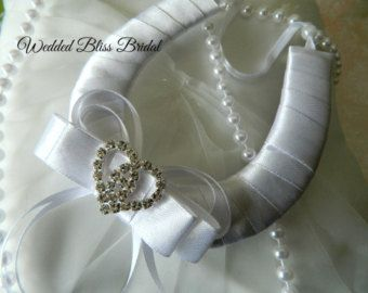 Classic Traditional horseshoe to adorn the brides arm on her Wedding day , a beautiful symbol to wish her happiness and to capture all the luck of the big day . Horseshoe is attached to a petite gift card for you to personalize with your well wishes . Beautiful horseshoe in White satin with white lace overylay , embellished with beaded lace flower motif , petite Faux Wedding ring and edged with organza frill and pearl trim. Presented in Organza keepsake pouch * Gift with purchase something…