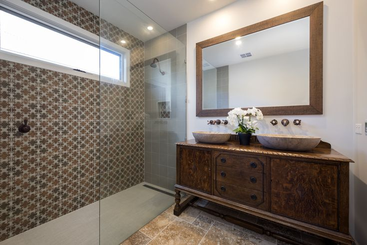 Bathroom, antique cabinet vanity, antique brass taps, timber framed mirror, patterned tiles, travertine stone basins