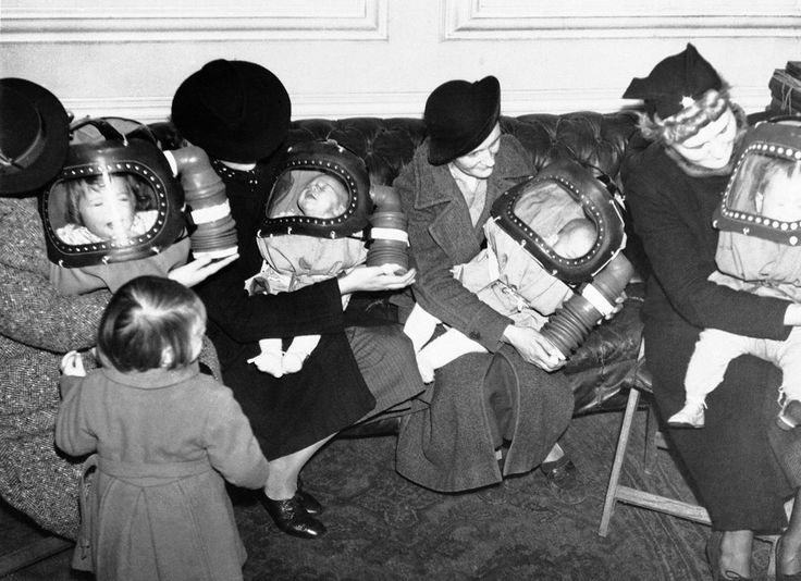 """This was the scene at Holborn Town Hall, in London, England, as officials and mothers tested the reactions of babies to a respirator designed to protect them against poison gas on March 3, 1939. Several babies, all under the age of two, were fitted with the """"baby helmets."""""""