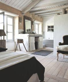 Dans cette chambre lumineuse, le parquet a été lasuré en blanc et la charpente peinte avec un blanc grisé.