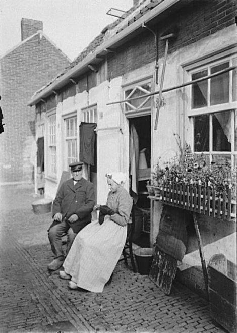 Keizerstraat 206, een echtpaar zit voor hun huisje in de Bloedpoort. ca 1913 zwartwitnegatief (glas). Door de firma Sjouke uitgegeven als prentbriefkaart #ZuidHolland #Scheveningen
