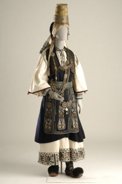 Bridal costume of the Pindus-mountain nomads worn by the Arvanitovlachs (Albanian-Vlachs) called the Karagounides of Epirus. It consists of a white chemise with embroidery at the hem and bib, a black segouni and a woven apron. Additional human hair braids, the headdress a tall cone-shaped hat with a silver band around its base as a diadem. Silver chains on the chest, a buckled belt (the kemeri) and bracelets [http://www.europeana.eu/portal/record/08540/_popup_php_photo_id_2643_lang_gr.html]