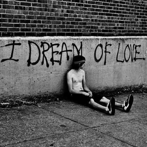 homeless man sitting by wall graffiti says I Dream Of Love.