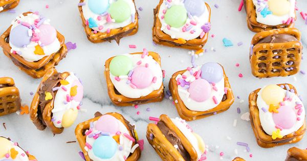Spring Rolo Pretzel Bites – Rolo candies sandwiched between two pretzel snaps and topped with white chocolate, pastel M&M's, and spring sprinkles.