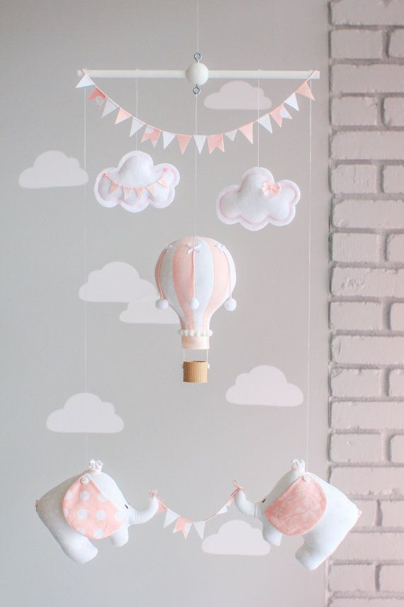 A little hot air balloon and two baby elephants hang from a wooden dowel. The little balloon is assembled with two different coordinating