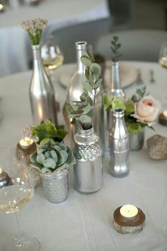 Centros de mesa hechos de botellas pintadas de color plata