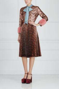 Платье из люрекса с отделкой из меха норки Gucci. Шелковое платье-миди с люрексом и сложным графичным принтом. Модель украшена манжетами из меха норки розового цвета. Важным элементом декора служит голубой бант, дополненный брошью. Носим эту модель с обувью на плоской подошве.