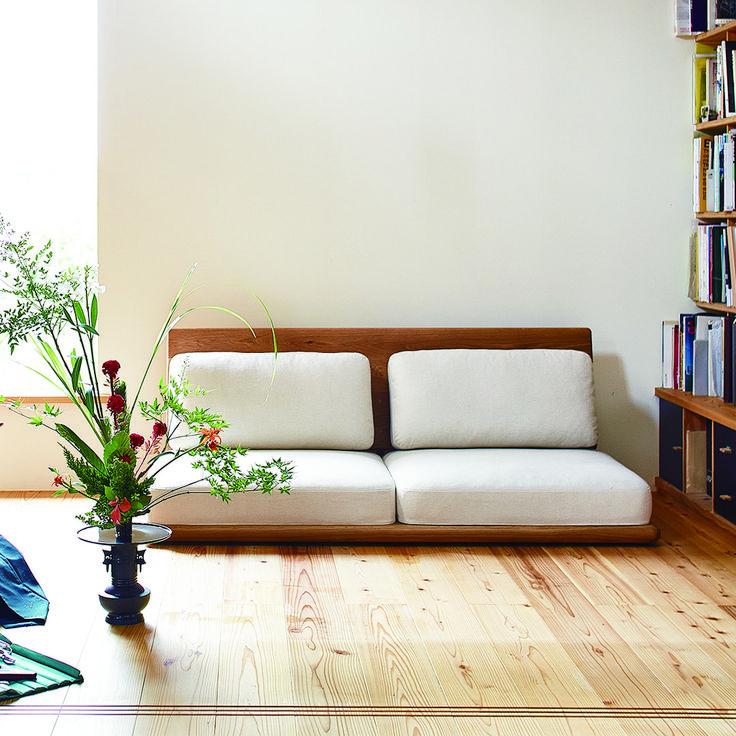 生け花とプレートソファ。木のぬくもりを大事にデザインしたソファなので、自然と美しく調和します。  こちらの作品は華道家の田中俊行さんによるもの。スタイルブック収録の「日本の床文化」対談(華道家×ヨガインストラクター)にもご参加いただいています。